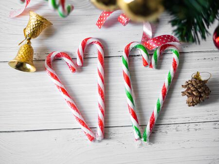 Heart shape christmas candy sticks and christmas tree on wooden table.