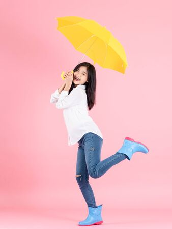 Asian teenager girl holding yellow umbrella during cold rainy day and jumping on pink background. Autumn concept