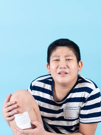 Injured Asian boy in pain receiving treatment with blue.
