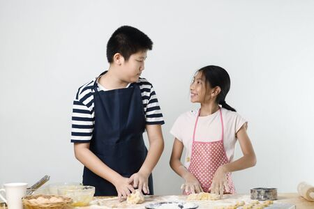 Asian preteen boy and girl preparing dough for making bread or pizza, lifestyle concept. Motion blur.