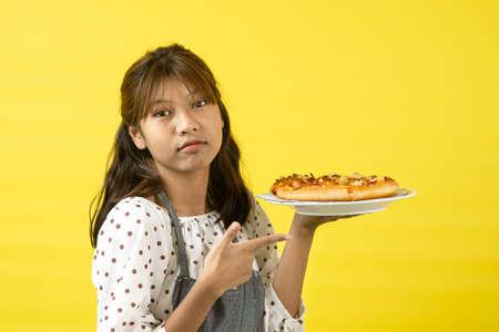 Asian teenager wearing apron holding pizza on yellow background. Standard-Bild