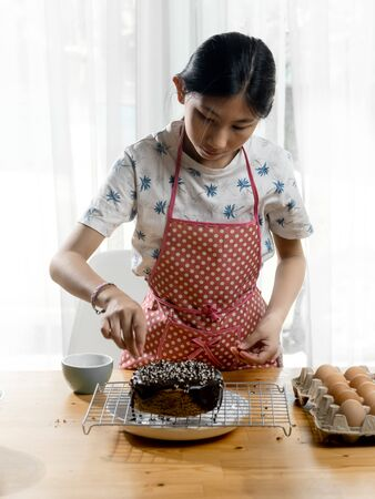 Happy Asian girl decorating homemade sponge cake at home, lifestyle and stay home concept.