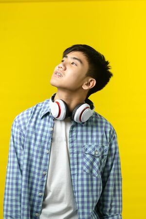 Asian teenager using headphone on yellow background.