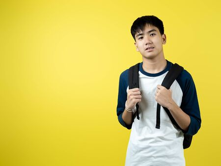 Asian teenager boy with backpack on yellow background