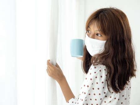 Asian teenager girl wearing mask holding coffee mug and looking out window, corona virus concept.
