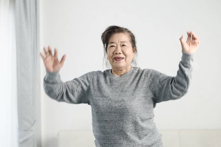 Asian senior woman doing exercise and dancing at home, stay home lifestyle concept. Motion blur.