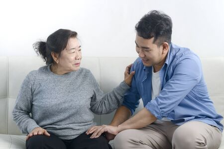 Asian man massage his mother at home, lifestyle concept. Standard-Bild