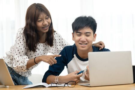 Asian teenager using  laptop and tablet for online schooling from home together, quarantine concept.