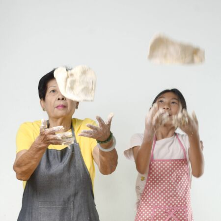 Asian senior woman and girl making dough for homemade pizza or bread, lifestyle concept. Motion blur. Standard-Bild