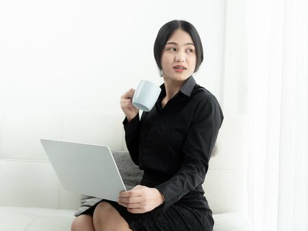 Asian woman in blank using laptop and drinks coffee sitting on sofa at home, quarantine concept.
