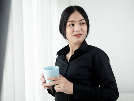 Asian business woman drinking coffee near window in the morning, lifestyle concept.