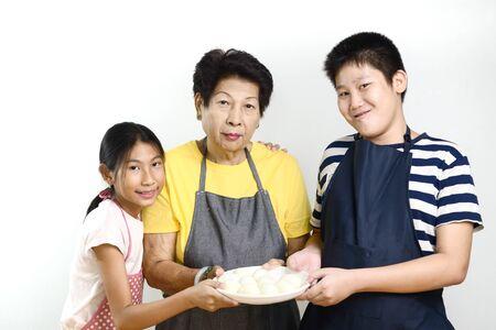 Asian senior woman teaching her grandchildren  peeled eggs, lifestyle concept.