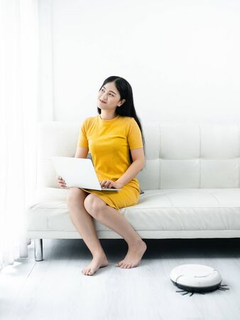 Modern life concept,  woman relaxing with laptop, automatic robotic hoover clean the room.