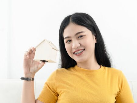 Asian woman holding house in her hands real estate concept.