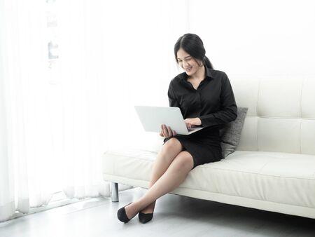 Asian woman in blank using laptop sitting on sofa at home, quarantine concept. Standard-Bild