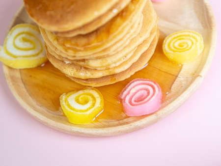 honey syrub on pancake stack on pink background.