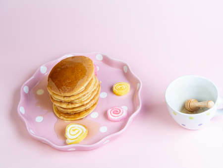 Pouring honey syrub on pancake stack on pink background.