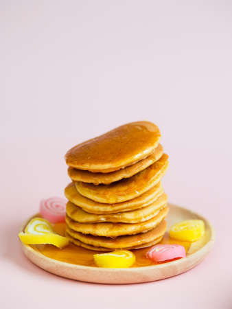 Pancake stack on wooden plate and pink background. Standard-Bild