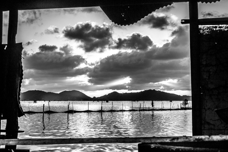 yo: Presenting a view through the old shack beside the lake Songkhla