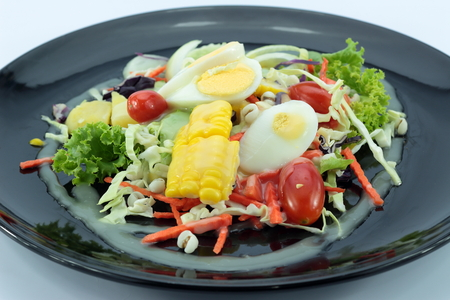 salad with chicken meat and eggs on Black plate isolated Stock Photo