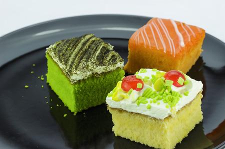 orange cake: Mini cakes, cream cakes and green tea, orange cake on a black plate