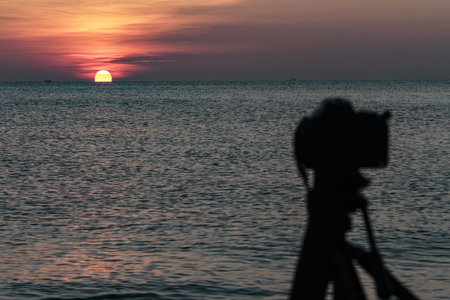 Camera on a tripod to take pictures of the sun and landscape Stock Photo