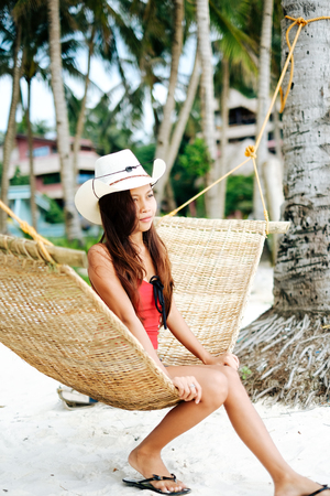 Beautiful young woman relaxing on ratan hammock on the white sand beach during travel vacation Stock Photo