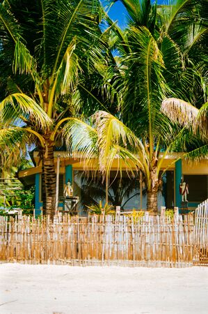 sugar palm: Nipa hot cottage over the fance with white sand beach on the tropical island