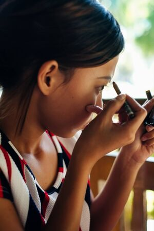 Young beautiful girl applying makeup. Girl coloring eyebrows with eyebrow liner