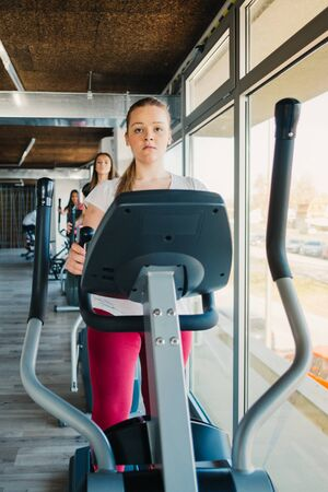 get a workout: Young beautiful girls exercising in the gym with ski machine