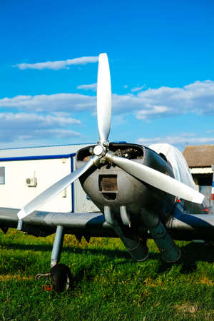 airplane ultralight: Gray airpane parked on the grass at the airfield