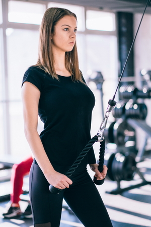 Fitness woman in the gym. Young woman doing fitness exercises in the gym, with lot machine Stock Photo