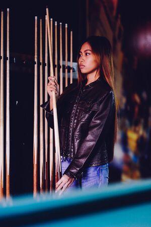 Jong mooi meisje dat leerjasje in een biljartclub draagt, met richtsnoerstok die voor het spel voorbereidingen treft