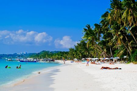 sugar palm: Beautiful tropical white sand beach with coconut palms and people on the beach