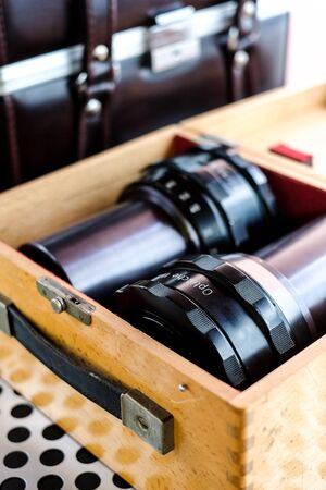 shutter aperture: Professional projector lenses in wooden storage box Stock Photo