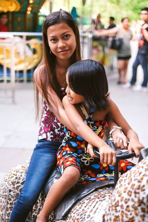 Sistersbonding in luna park riding a toy car