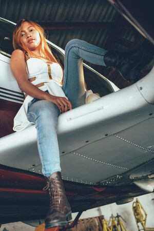 airfield: Beautiful female portrait in the airplane hangar, with modern aircraft Stock Photo