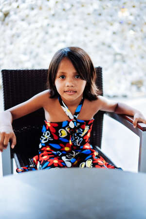Young little cute girl sitting on the chair alone waiting