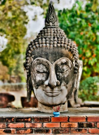 veda: Buddha head with offerings at Wat Phutthaisawan temple in Ayutthaya Historical Park