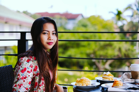 Beautiful young girl eating lunch in outdoors cafe at summer day Stock Photo