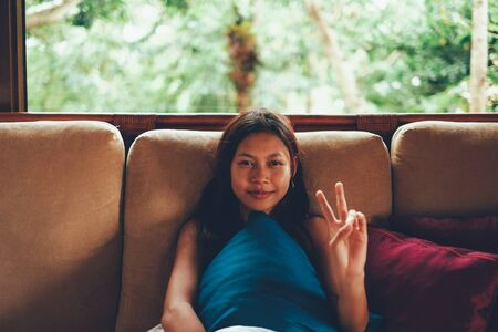 Young Asian woman during vacation relaxing on the sofa with big window behind her. woman on summer vacation in Bali