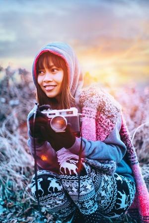 Fotógrafo fêmea novo no tempo frio que veste a camiseta e o lenço colorido durante o por do sol da tarde fora Foto de archivo