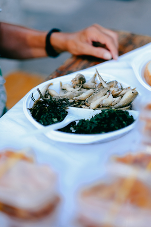 Fresh and fried sardine fish in a plate with green vegetable salad