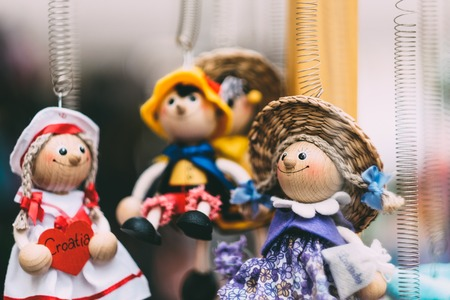 Wooden dolls dressed in diffirent outfits. handmade wooden dolls hanging as a display. decirative dolls
