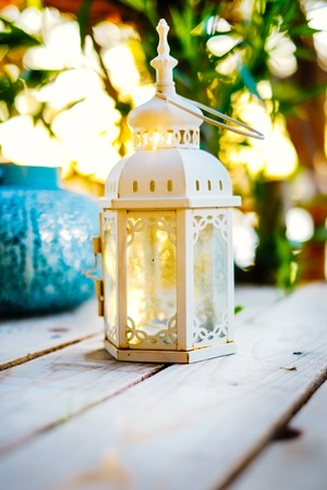 Closeup decorative white candle lantern on wooden table with beautiful sunset
