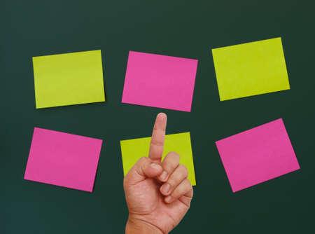 Hand pointing on blank notepad on blackboard Stock Photo - 13076962