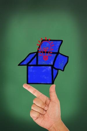 Hand hold on blue box and light bulb on blackboard Stock Photo - 13450089