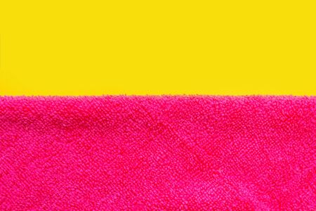 the separation between the yellow background and pink. cleaning cloth pink. space for text