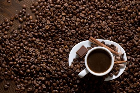 Cup of coffee with chocolate on coffee beans, view from above
