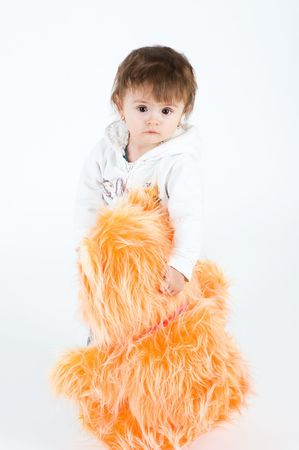 Serious looking girl standing with big orange furry bear. Isolated on white photo